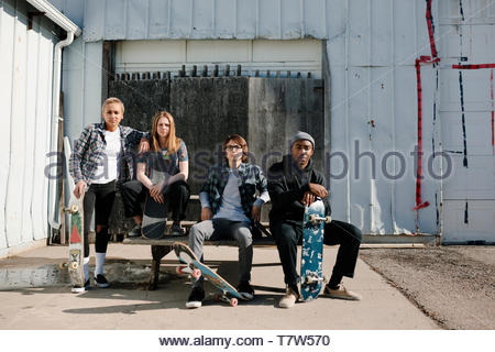 Portrait confident, cool young skateboarder friends in sunny parking lot - Stock Photo