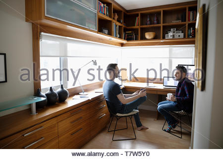 Male gay couple working from home, talking in home office - Stock Photo