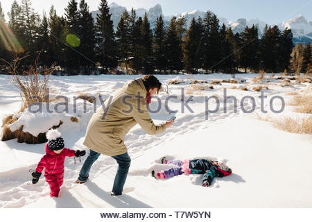 Family playing in snow, making snow angel - Stock Photo