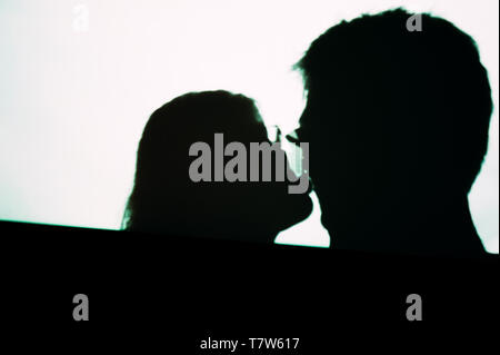 Abstract background shadows of people man and woman kissing on digital wall light from cinema projector on a wall black and white image - Stock Photo