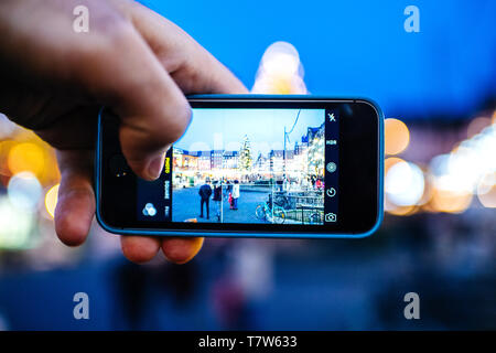 Strasbourg, France - Dec 27, 2017: Man hand POV holding taking photo of the central square of Place Kleber in Strasbourg with decorated for Christmas fir tree and people having fun - Stock Photo