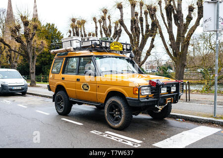 Strasbourg, France - Dec 27, 2017: Side view of new vintage yellow Land Rover Defender Camel Trophy with luggage on the roof parked in central city street - Stock Photo