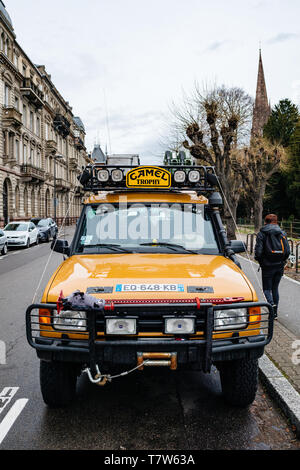 Strasbourg, France - Dec 27, 2017: Front view of vintage yellow Land Rover Defender Camel Trophy with luggage on the roof parked in central city street with - Stock Photo