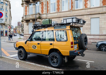 Strasbourg, France - Dec 27, 2017: Rear view of new vintage yellow Land Rover Defender Camel Trophy with luggage on the roof parked in central city street with - Stock Photo