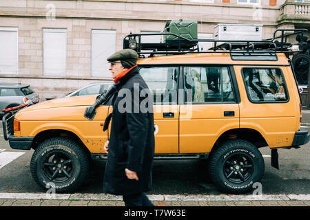 Strasbourg, France - Dec 27, 2017: Senior man walking near new vintage yellow Land Rover Defender Camel Trophy with luggage on the roof parked in central city street with - Stock Photo