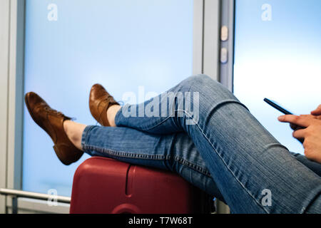 Relaxed woman using smartphone telephone with legs being relaxed on the red luggage waiting for the flight in Airport terminal - Stock Photo