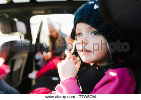 Cute toddler girl in back seat of car - Stock Photo