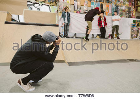 Young man with camera photographing friends skateboarding at indoor skate park - Stock Photo