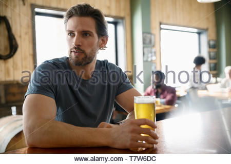 Man drinking beer in brewhouse - Stock Photo