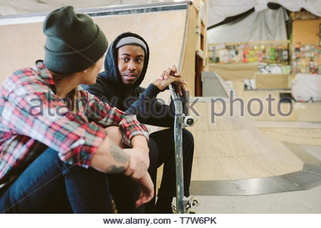 Friends talking at indoor skate park - Stock Photo