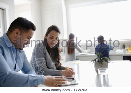 Couple using digital tablet in kitchen while children do dishes at sink - Stock Photo