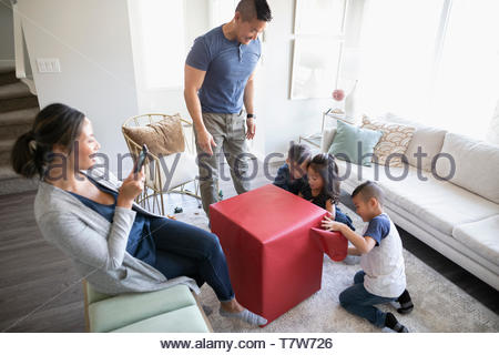 Family opening gift in living room - Stock Photo