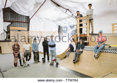 Portrait confident young friends skateboarding at indoor skate park - Stock Photo