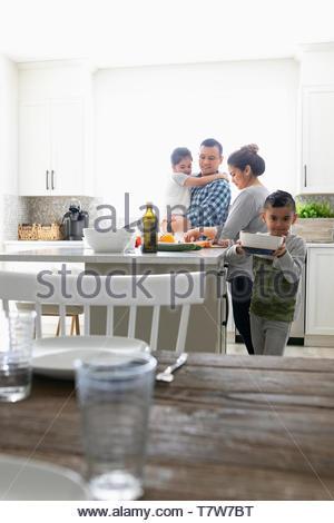Family preparing dinner in kitchen - Stock Photo