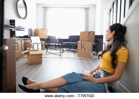 Woman taking a break from moving house, drinking coffee on floor - Stock Photo