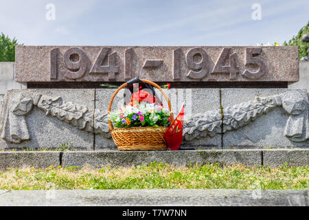 Flowers in front of a Second World War grave of a fallen Soviet soldier at the Soviet War Memorial in Berlin Treptow on Liberation Day, Germany - Stock Photo