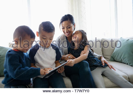 Happy mother and children using digital tablet on living room sofa - Stock Photo