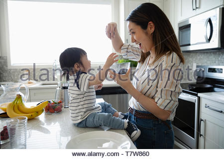 Mother and toddler daughter eating blueberries in kitchen - Stock Photo