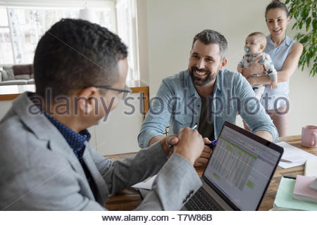 Financial planner and couple with baby meeting in dining room - Stock Photo