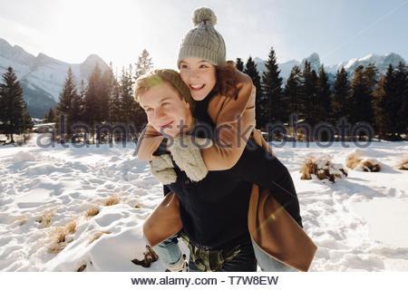 Happy teenage couple piggybacking in snow - Stock Photo
