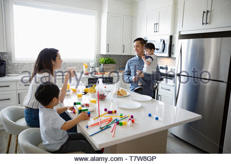 Family eating breakfast and playing with toys in morning kitchen - Stock Photo