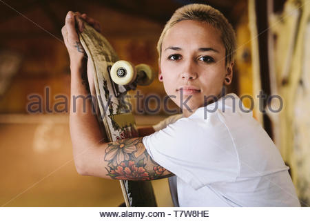 Portrait confident, tough young female skateboarder with tattoo at indoor skate park - Stock Photo