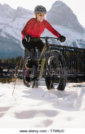 Woman fat biking in snow - Stock Photo