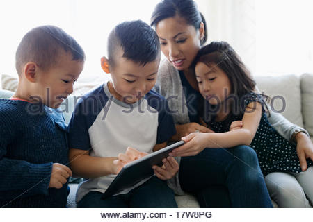 Mother and children using digital tablet on sofa - Stock Photo