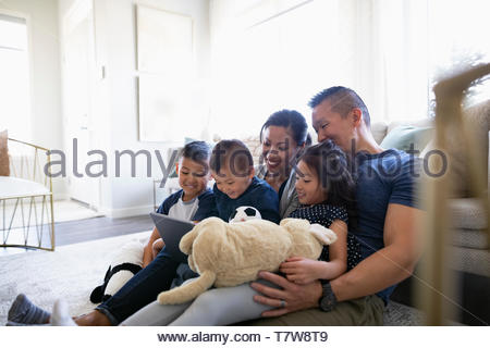 Family using digital tablet in living room - Stock Photo