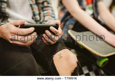 Close up teenage skateboarders with tattoos using smart phone - Stock Photo