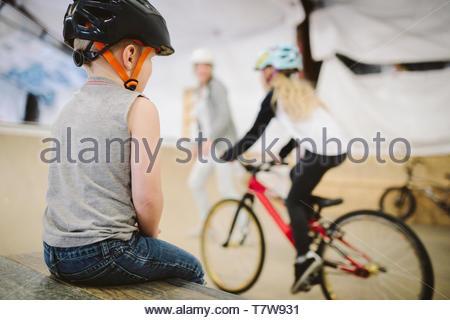 Toddler boy watching sister bike riding at indoor skate park - Stock Photo