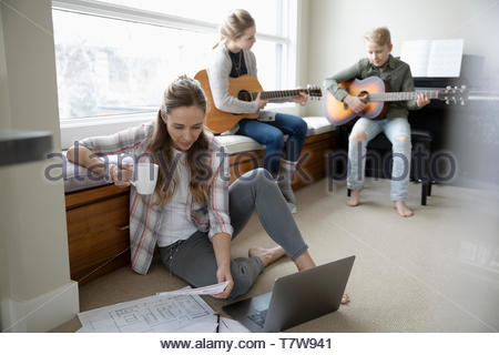 Mother working from home while children practice guitar in background - Stock Photo