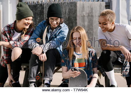 Women skateboarders hanging out, using smart phone at sunny skate park - Stock Photo