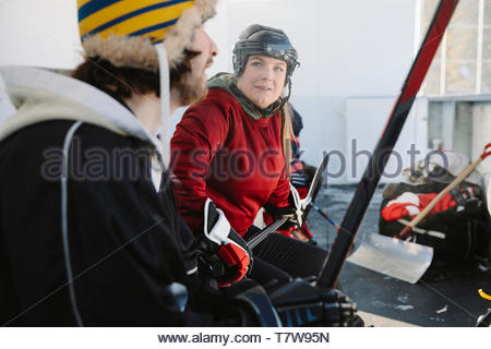 Friends playing outdoor ice hockey, sitting on sideline bench - Stock Photo