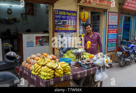 Street scene in Mahipalpur district, a suburb by Delhi Airport in New Delhi, capital city of India: local male street trader at a barrow of fruits - Stock Photo