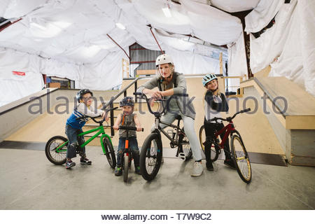 Portrait confident mother and children on bmx bikes at indoor skate park - Stock Photo