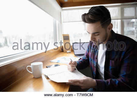 Focused young man working in home office, checking schedule calendar - Stock Photo