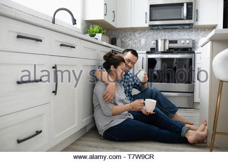 Affectionate couple drinking coffee on kitchen floor - Stock Photo