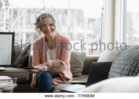 Portrait smiling, confident senior woman working from home, using smart phone and laptop on sofa - Stock Photo