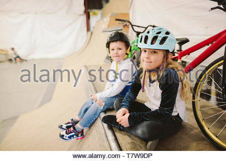 Portrait brother and sister with bmx bikes sitting at top of ramp at indoor skate park - Stock Photo