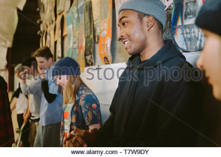 Young friends hanging out at indoor skate park - Stock Photo