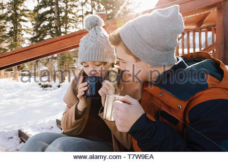 Affectionate young couple drinking hot chocolate on snowy steps - Stock Photo