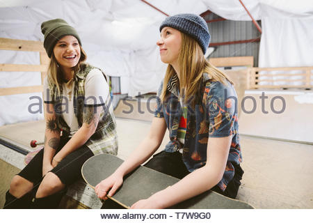 Teenage girl friends with skateboards talking at indoor skate park - Stock Photo