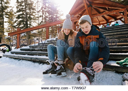 Young couple tying ice skates on snowy steps - Stock Photo