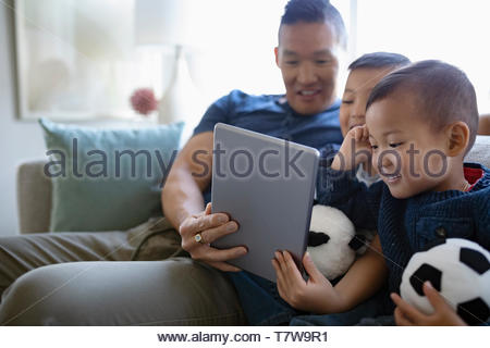 Father and sons using digital tablet on living room sofa - Stock Photo