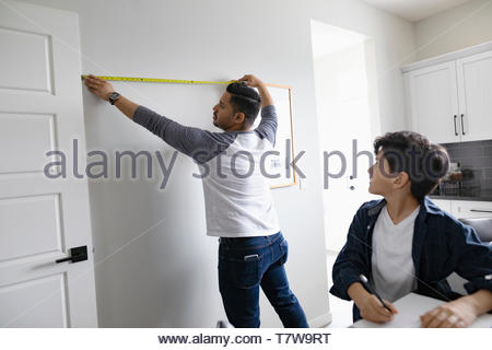 Father and son measuring wall with tape measure for diy project - Stock Photo