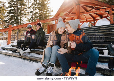 Affectionate teenage couple drinking hot cocoa, taking a break from ice skating - Stock Photo