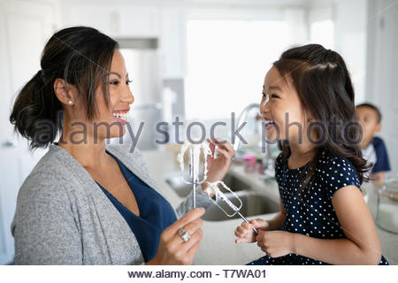 Happy, playful mother and daughter baking, holding beaters with frosting - Stock Photo