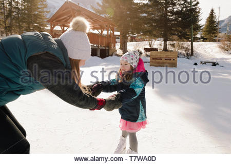 Mother and daughter holding hands, ice skating on frozen pond - Stock Photo