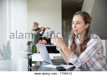 Thoughtful woman drinking coffee, working from home while son practices violin in background - Stock Photo
